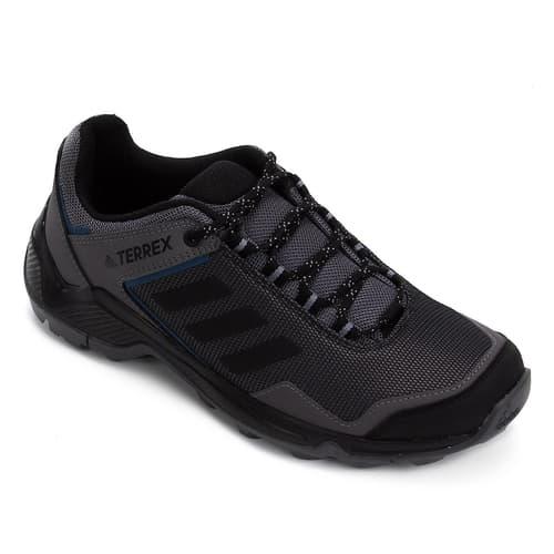A foto mostra um pé do tênis Adidas, modelo Terrex, da cor preta.