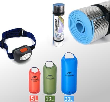 Foto com uma lanterna de cabeça, sacos estanques e um isolante térmico prateado
