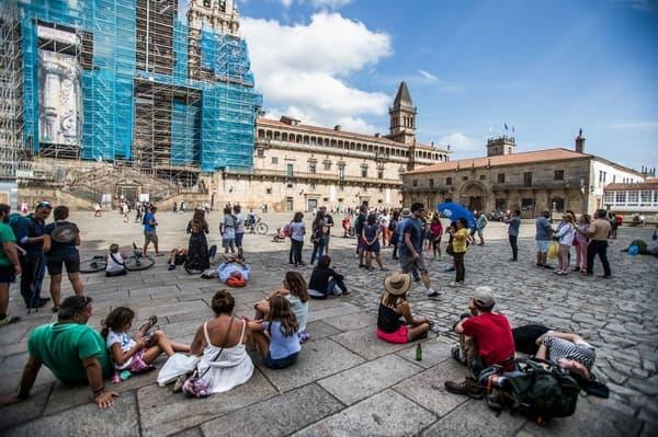 Vários peregrinos sentados na praça do Obradoiro, em Santiago de Compostela, na frente da Catedral