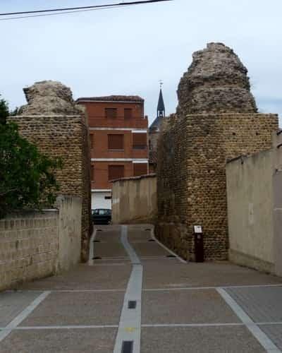 Na foto aparecem algo que parece ser o que restou de dois grandes pilares de uma antiga muralha de pedra, com uma pequena rua entre elas. Esta é a entrada dos peregrinos em Mansilla de las Mulas.