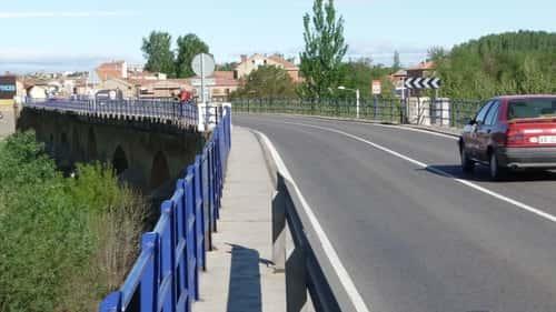 A foto mostra a ponte antiga, chegando em Puente Villarente, onde há uma estreita passagem para os pedestres ao lado da via dos carros.