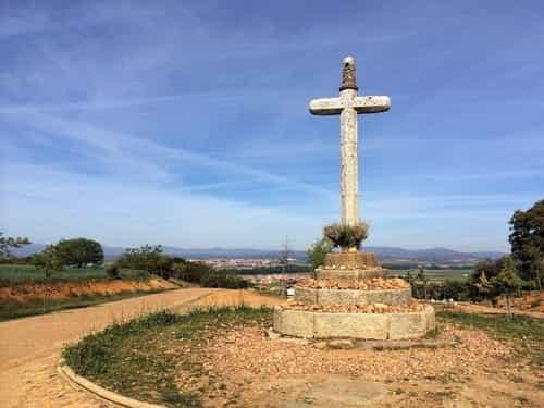 A foto mostra uma cruz de pedra e, ao fundo, as cidades de San Justo de la Vega e Astorga.