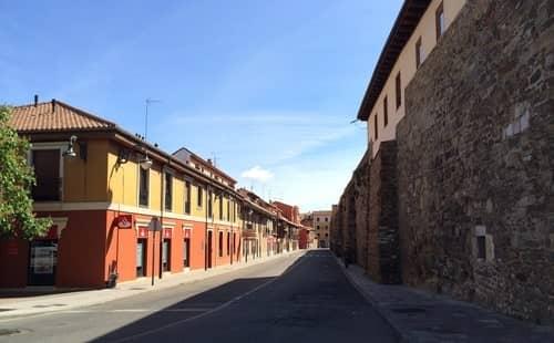 Foto mostrando uma rua com uma muralha de pedra, em Léon, Espanha.