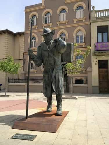 A foto mostra a escultura de um peregrino, em bronze, e o albergue Siervas de Maria, de Astorga, no fundo.