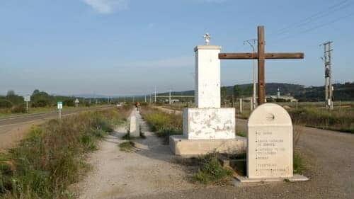 Foto da trilha para peregrinos na etapa entre Astorga e Rabanal del Camino. Ao lado da trilha, duas cruzes e a indicação dos pueblos pelos quais o peregrino pasará.