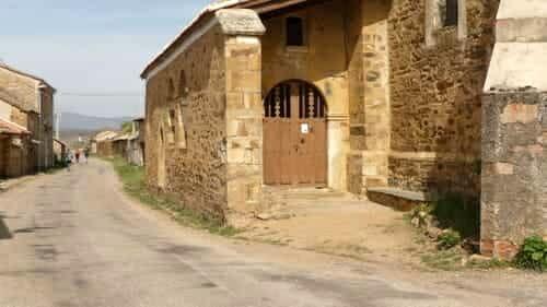 Foto da porta de entrada da igreja de Santiago, em El Ganso, com a estrada por onde os peregrinos caminham ao lado esquerdo da igreja.