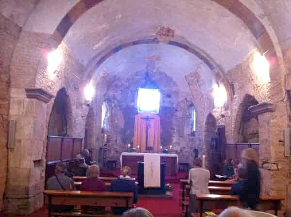Na foto aparece o interior da igreja da Assunção. Ela é toda feita de pedra, não é muito grande. Poucas pessoas estão aguardando sentadas o início da missa, que é em canto gregoriano.