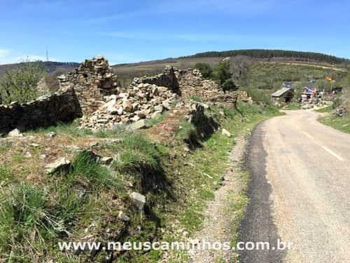 Foto mostra uma estrada o albergue de Manjarin ao fundo, no Caminho de Santiago.