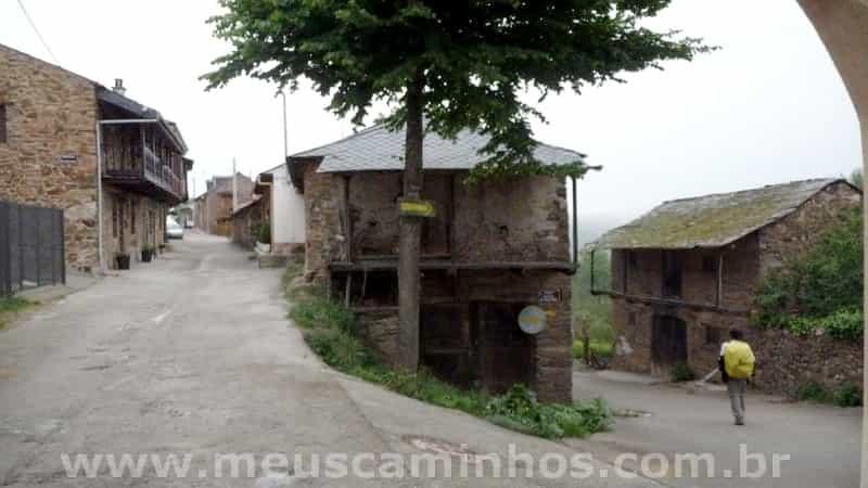 Foto do pueblo de Riego de Ambrós, mostra que o lugar é uma descida constante. Aparece um peregrino na parte de baixo da rua.