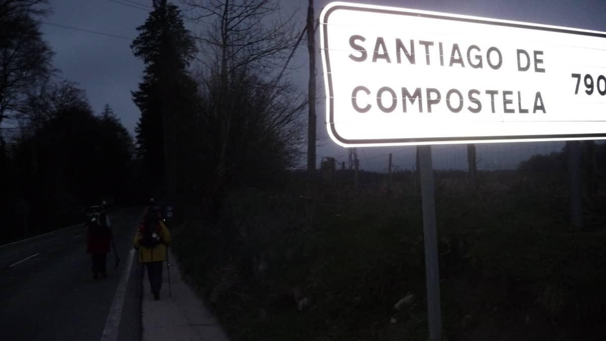 """Foto mostrando dois peregrinos caminhando ao lado de uma placa com os dizeres: """"Santiago de Compostela, 790 quilômetros""""."""